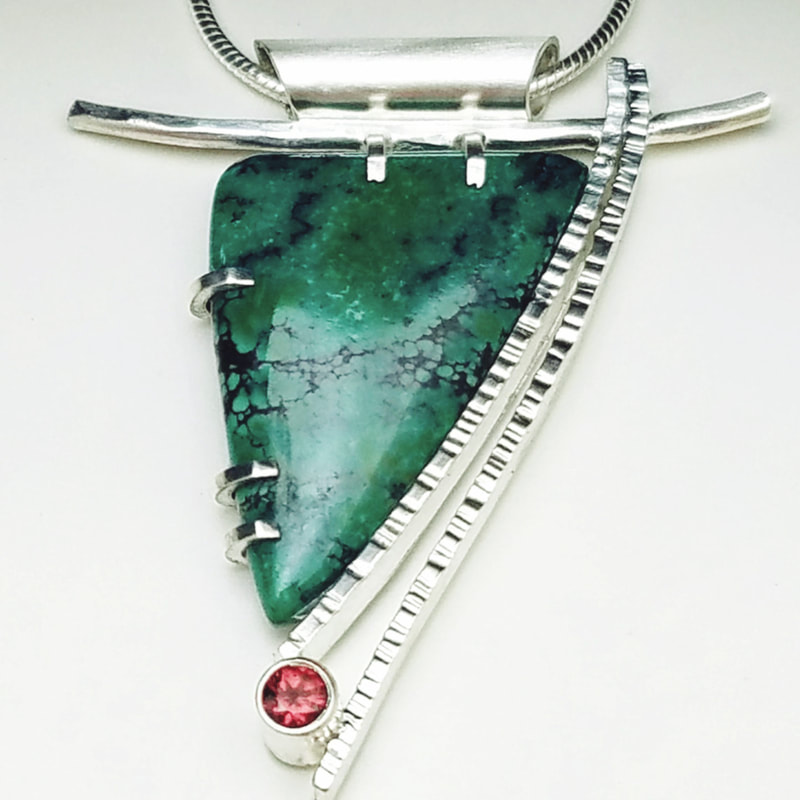 Artistic Turquoise pendant with textured lines and a red gemstone on the bottom